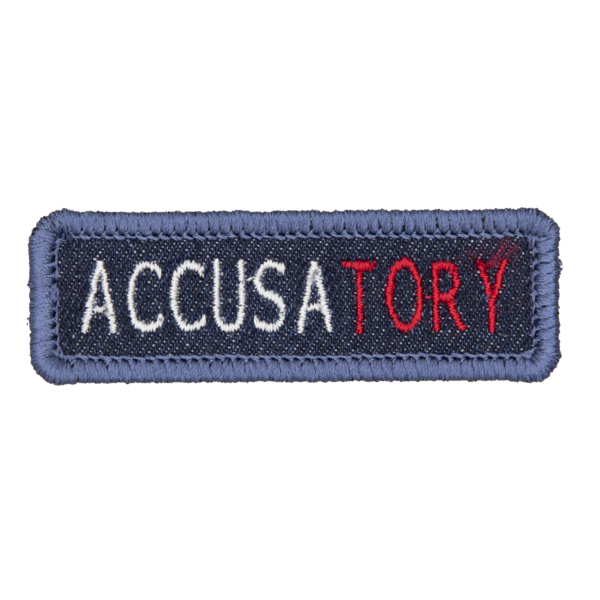 blue denim patch embroidered with the word ACCUSATORY