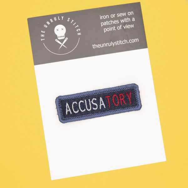 postcard with blue denim patch embroidered with the word ACCUSATORY