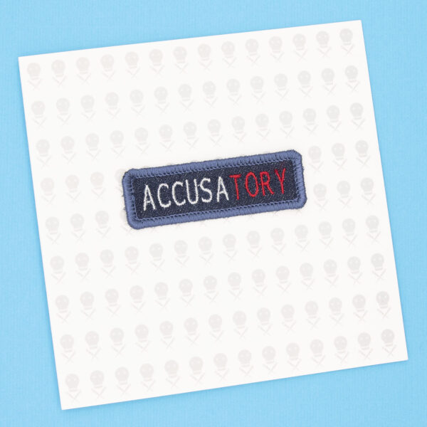 gift card with blue denim patch embroidered with the word ACCUSATORY