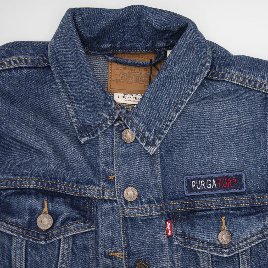 denim jacket and blue denim patch embroidered with the word PURGATORY patches as protest