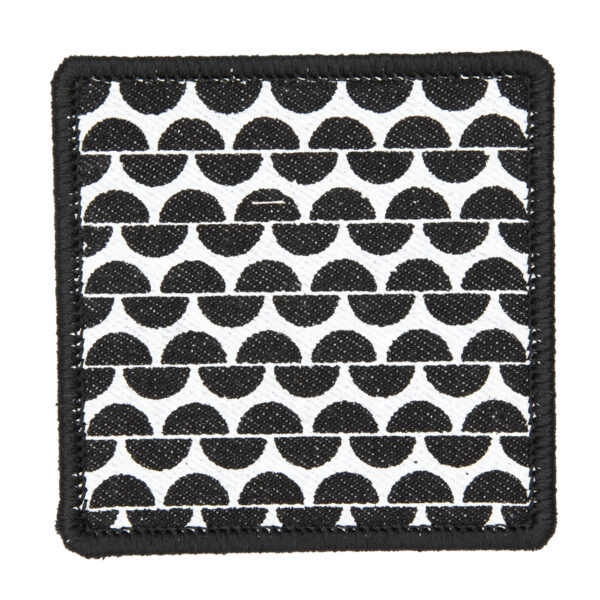 patch made from black denim screen printed with a garter stitch print and finished with an embroidered border