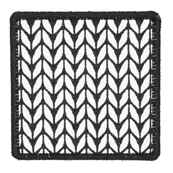 patch made from black denim screen printed with a stocking stitch print and finished with an embroidered border