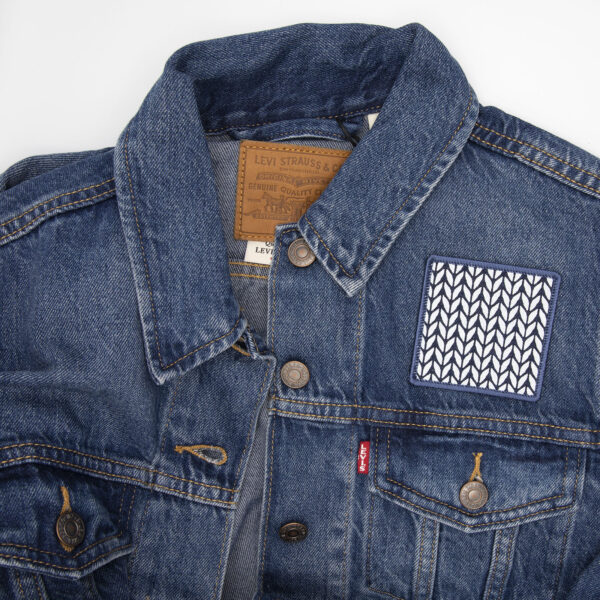 patch made from blue denim screen printed with a stocking stitch print and finished with an embroidered border