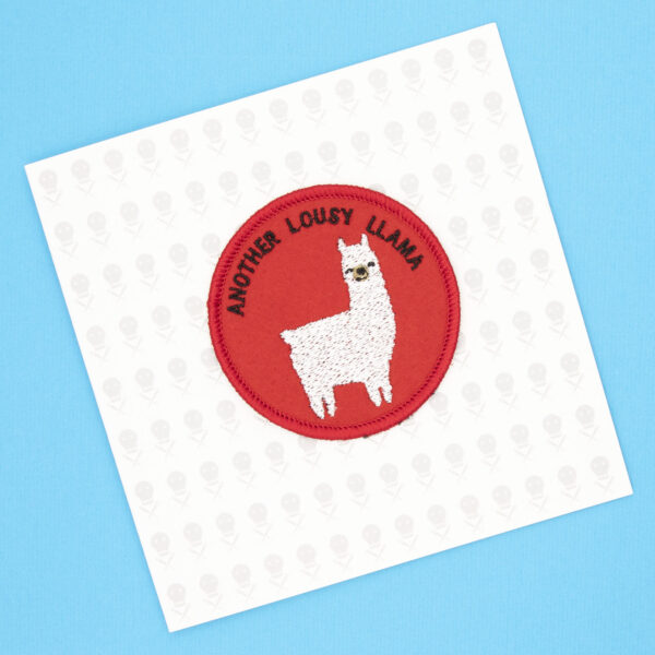 round embroidered patch picture of a white llama and text another lousy llama on red