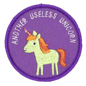 round embroidered patch picture of a green unicorn and text another useless unicorn on purple