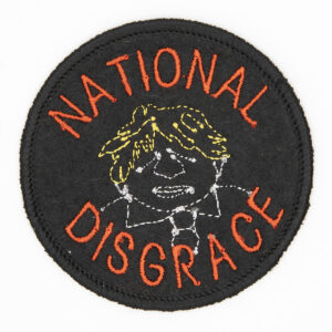 round embroidered patch line drawing of Boris Johnson and the words National Disgrace