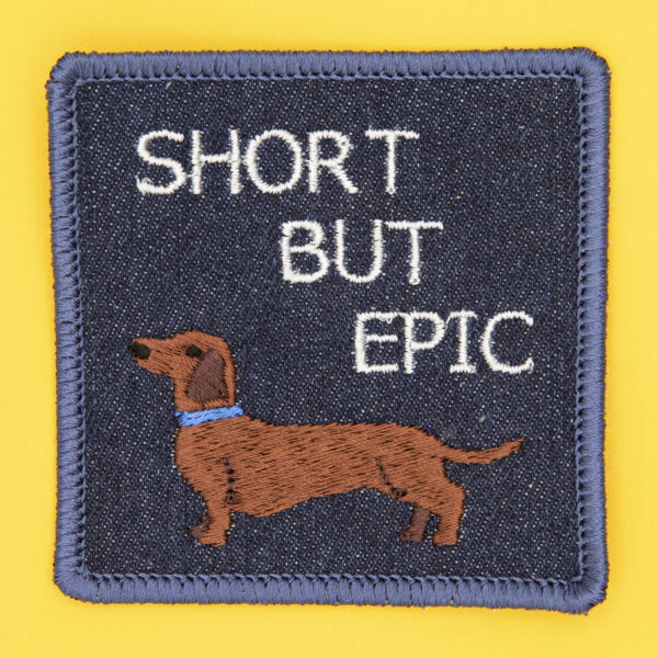 square embroidered patch picture of dachshund dog and text short but epic on blue denim
