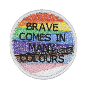 Round embroidered patch, embroidered with a silver border and pride rainbow stripes. The words BRAVE COMES IN MANY COLOURS in black text sit in top of the stripes.Photographed on a white background