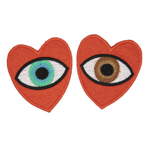 large embroidered patches , pair of red hearts, one containing a brown eye and one containing a blue eye photographed on a white background