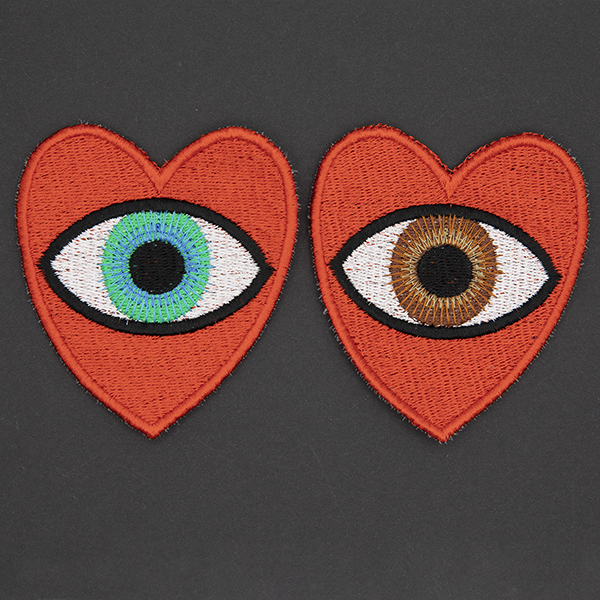 large embroidered patches , pair of red hearts, one containing a brown eye and one containing a blue eye photographed on a black background