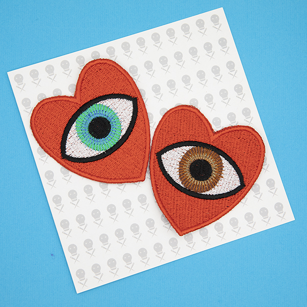 large embroidered patches , pair of red hearts, one containing a brown eye and one containing a blue eye photographed on a gift card printed with tiny images of The Unruly Stitch logo