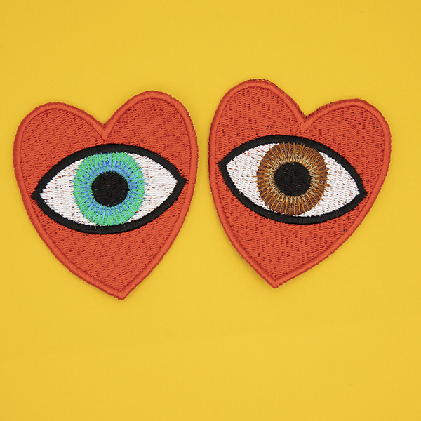 large embroidered patches , pair of red hearts, one containing a brown eye and one containing a blue eye photographed on a sunshine yellow background