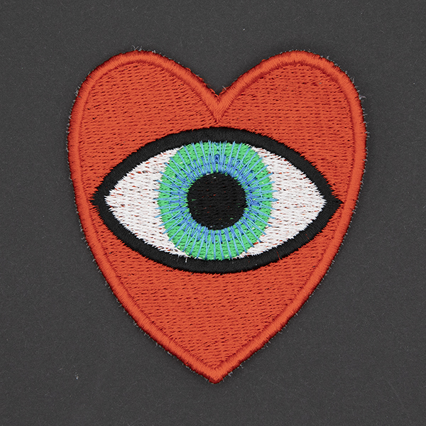 large embroidered patch, red heart containing a blue eye photographed on a black background