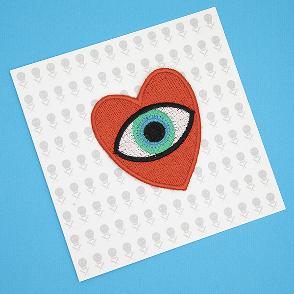 large embroidered patch, red heart containing a blue eye photographed on a gift card printed with tiny images of The Unruly Stitch logo