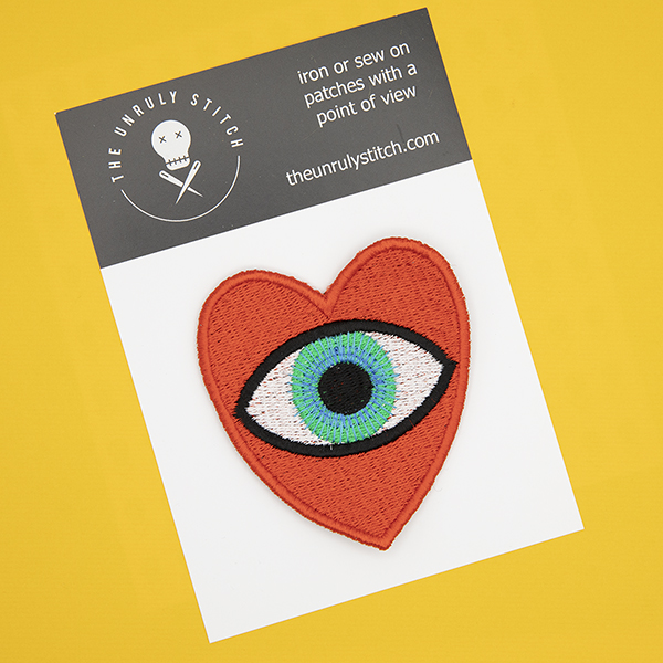 large embroidered patch, red heart containing a blue eye photographed on a black and white postcard printed with The Unruly Stitch logo