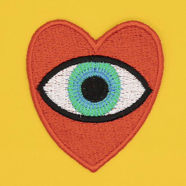 large embroidered patch, red heart containing a blue eye photographed on a sunshine yellow background