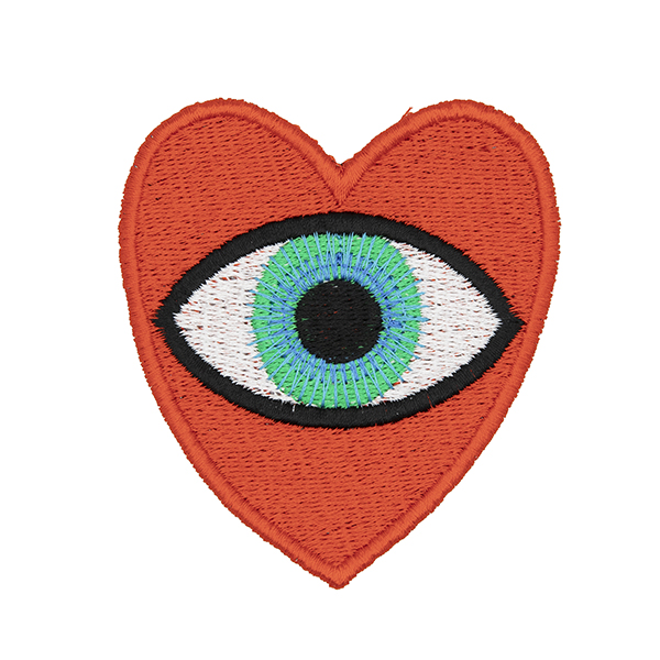 large embroidered patch, red heart containing a blue eye photographed on a white background