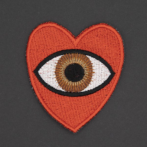 large embroidered patch, red heart containing a brown eye photographed on a black background