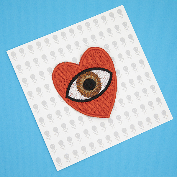 large embroidered patch, red heart containing a brown eye photographed on a gift card printed with tiny images of The Unruly Stitch logo
