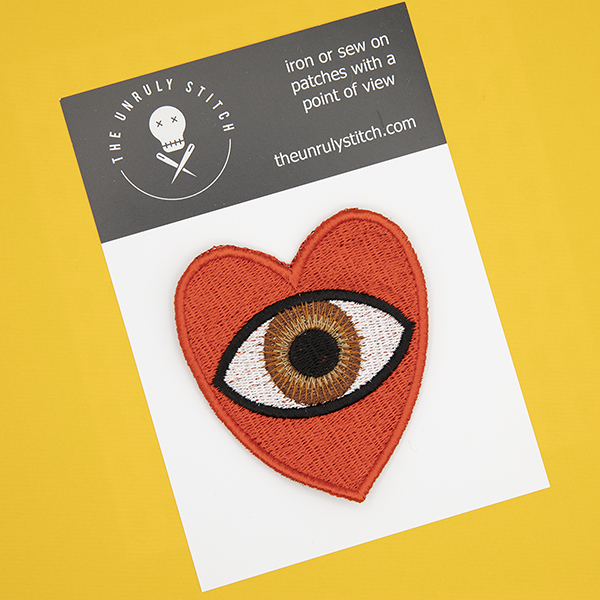 large embroidered patch, red heart containing a brown eye photographed on a black and white postcard with The Unruly Stitch logo