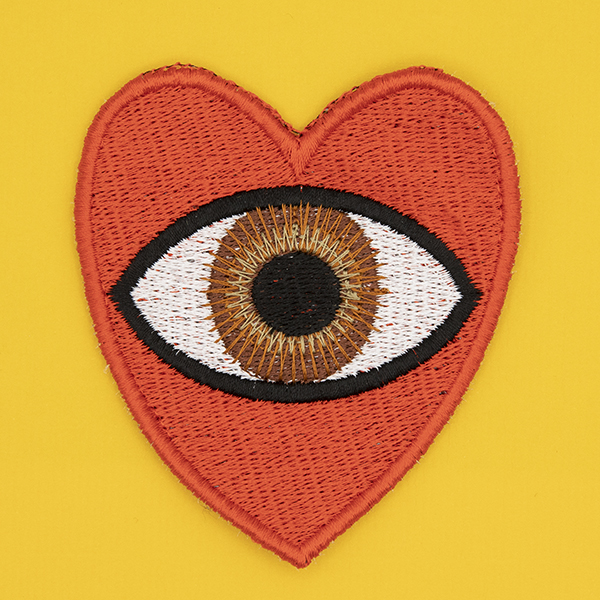 large embroidered patch, red heart containing a brown eye photographed on a sunshine yellow background