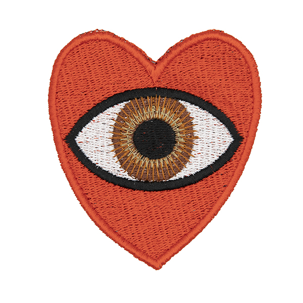 large embroidered patch, red heart containing a brown eye photographed on a white background