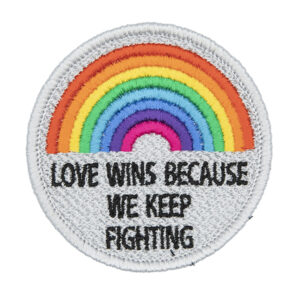 round embroidered patch, embroidered in silver with an eight colour rainbow and the words LOVE WINS BECAUSEWE KEEP FIGHTING in black text photographed ona white background