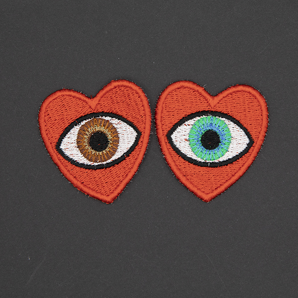 medium embroidered patches , pair of red hearts, one containing a brown eye and one containing a blue eye photographed on a black background