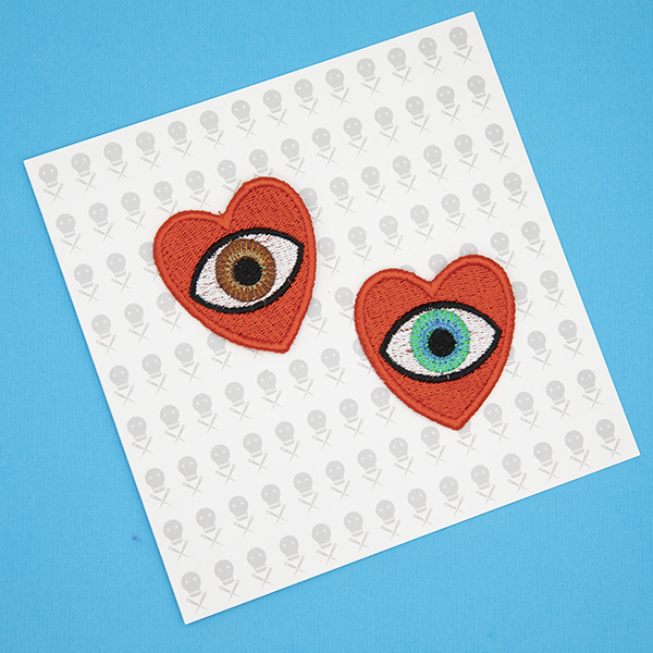 medium embroidered patches , pair of red hearts, one containing a brown eye and one containing a blue eye photographed on a gift card printed with tiny images of The Unruly Stitch logo