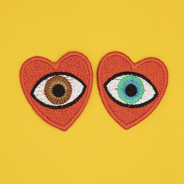 medium embroidered patches , pair of red hearts, one containing a brown eye and one containing a blue eye photographed on a sunshine yellow background