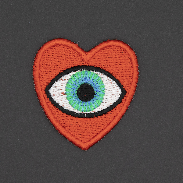 medium embroidered patch, red heart containing a blue eye photographed on a black background