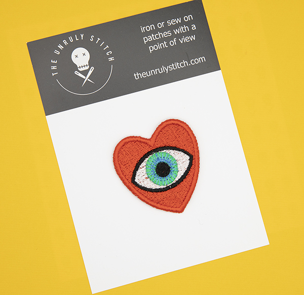 medium embroidered patch, red heart containing a blue eye photographed on a black and white postcard printed with The Unruly Stitch logo