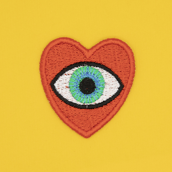 medium embroidered patch, red heart containing a blue eye photographed on a sunshine yellow background