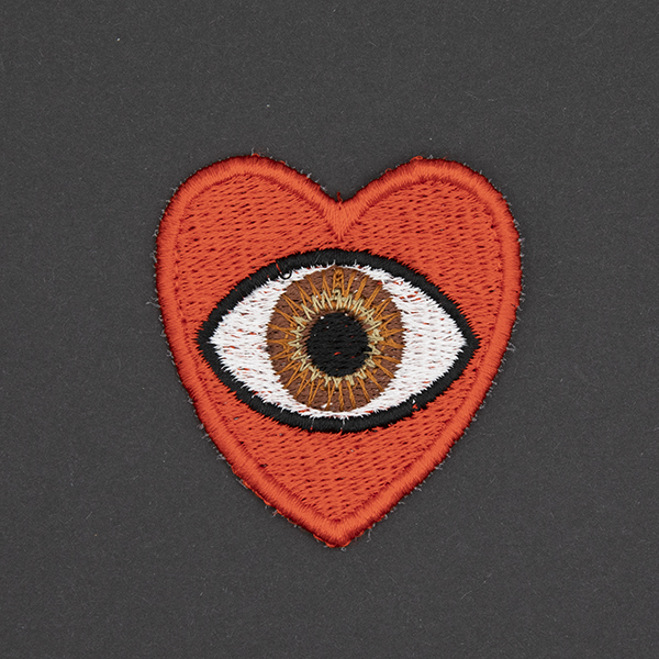 medium embroidered patch, red heart containing a brown eye photographed on a black background