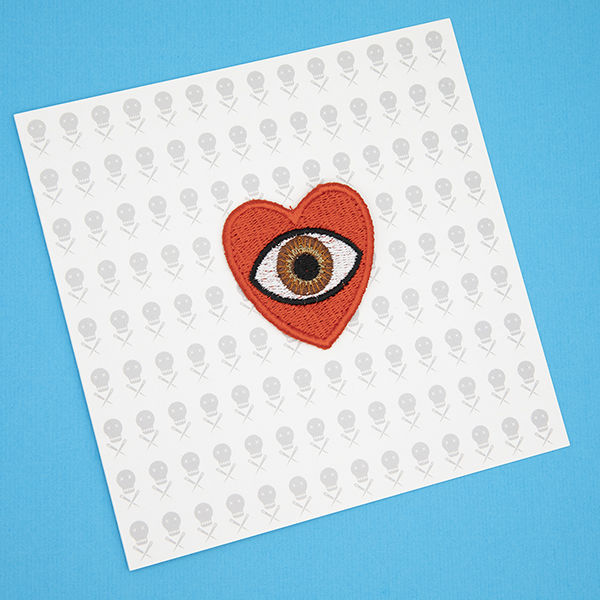 medium embroidered patch, red heart containing a brown eye photographed on a gift card printed with The Unruly Stitch logo
