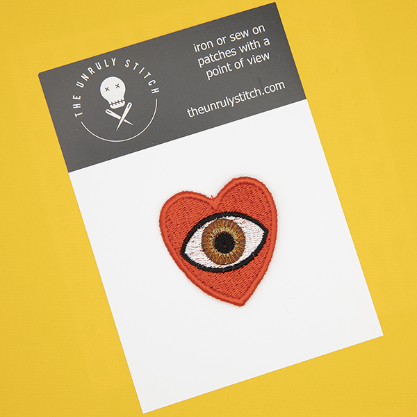 medium embroidered patch, red heart containing a brown eye photographed on a black and white postcard with The Unruly Stitch logo