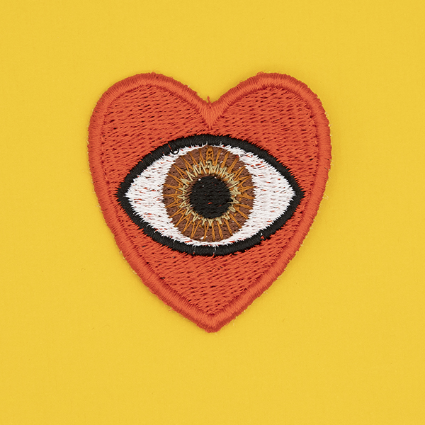 medium embroidered patch, red heart containing a brown eye photographed on a sunshine yellow background