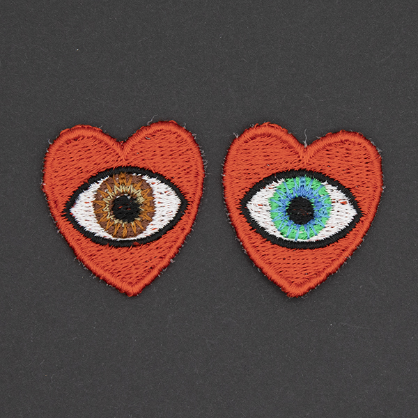 small embroidered patches , pair of red hearts, one containing a brown eye and one containing a blue eye photographed on a black background