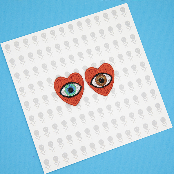 small embroidered patches , pair of red hearts, one containing a brown eye and one containing a blue eye photographed on a gift card with The Unruly Stitch logo