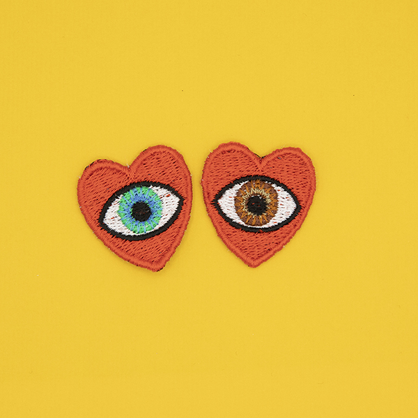 small embroidered patches , pair of red hearts, one containing a brown eye and one containing a blue eye photographed on a sunshine yellow background