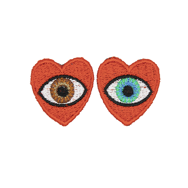 small embroidered patches , pair of red hearts, one containing a brown eye and one containing a blue eye photographed on a white background