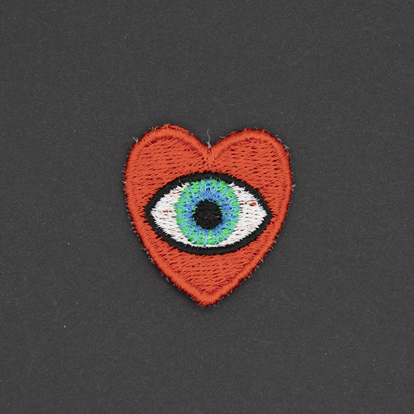 small embroidered patch, red heart containing a blue eye photographed on a black background