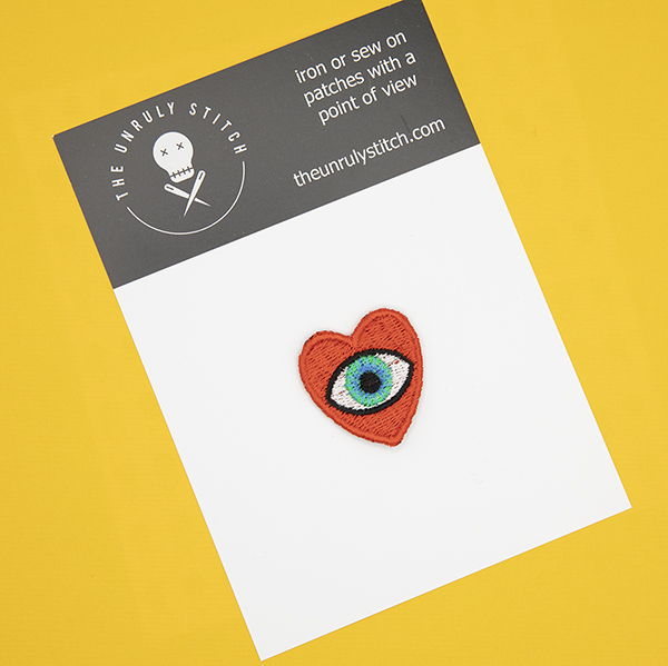 small embroidered patch, red heart containing a blue eye photographed on a black and white postcard with The Unruly Stitch logo