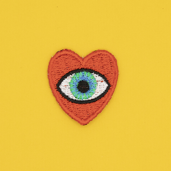 small embroidered patch, red heart containing a blue eye photographed on a sunshine yellow background
