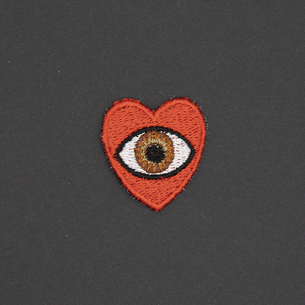 small embroidered patch, red heart containing a brown eye photographed on a black background