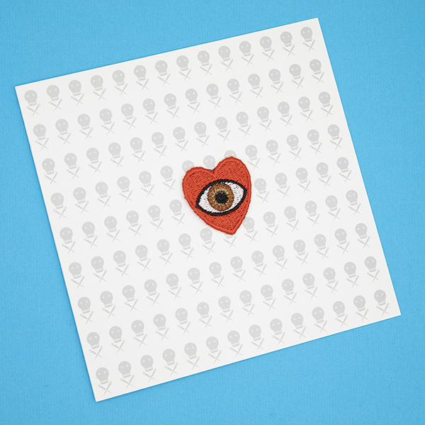 small embroidered patch, red heart containing a brown eye photographed on a gift card with tiny images of The Unruly Stitch logo