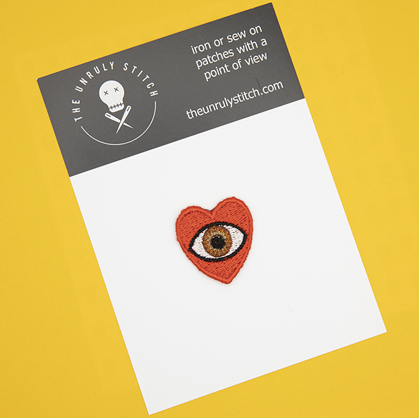 small embroidered patch, red heart containing a brown eye photographed on a black and white postcard with The Unruly Stitch logo