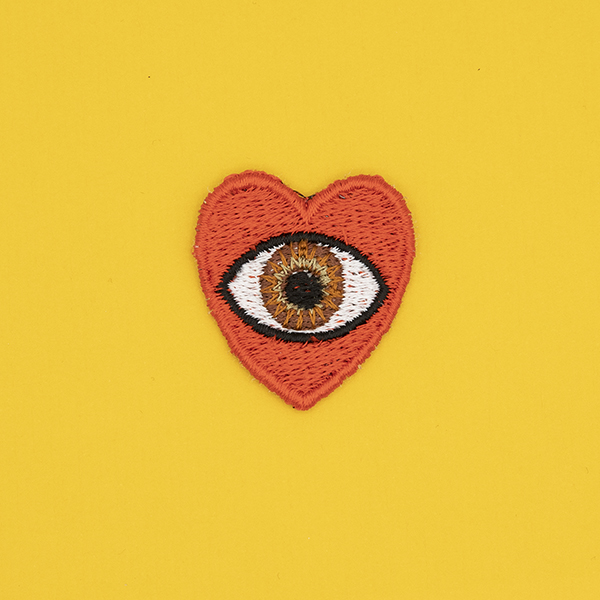 small embroidered patch, red heart containing a brown eye photographed on a sunshine yellow background