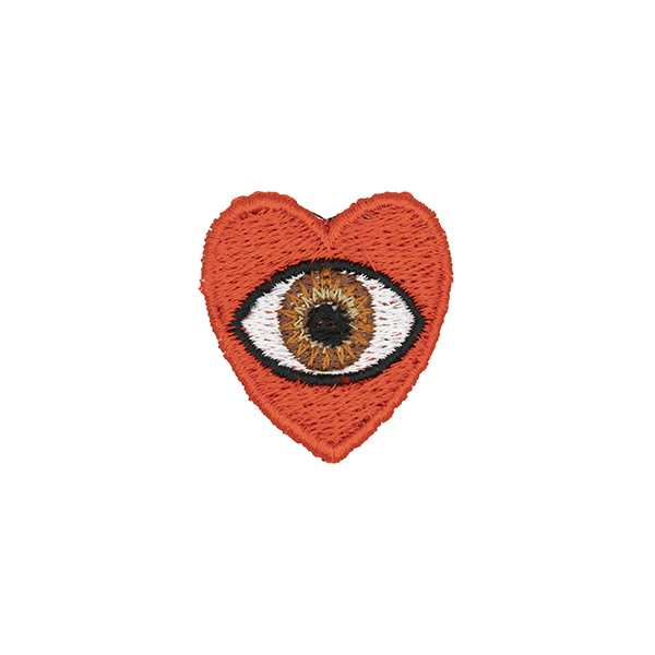 small embroidered patch, red heart containing a brown eye photographed on a white background