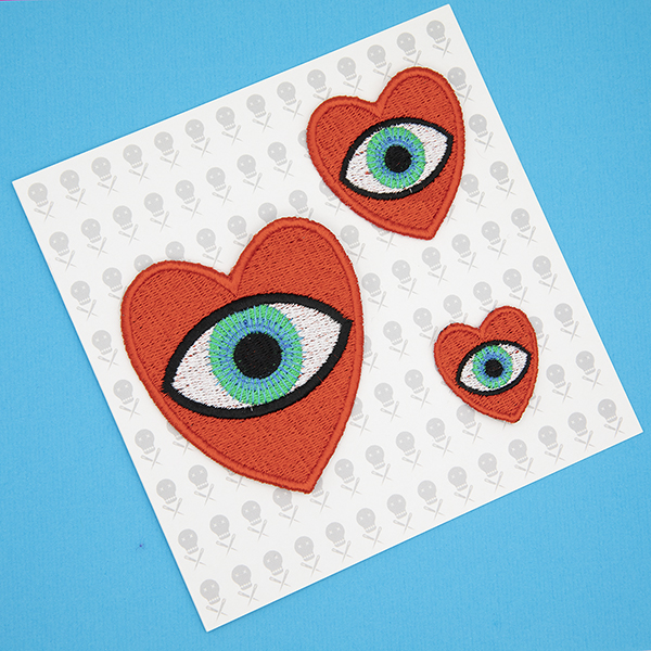 three embroidered patches, all read hearts with blue eye in the centre. Patches are large, medium and small. Displayed in a gift card which features tiny images of The Unruly Stitch logo on a white background.